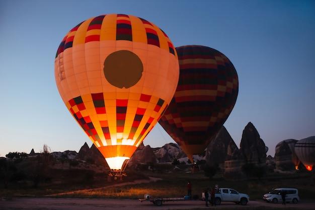 Inflating hot air balloons at dawn