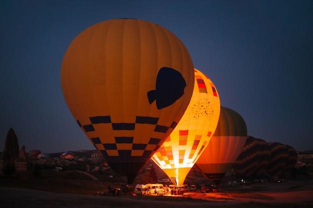 Inflating hot air balloons at night