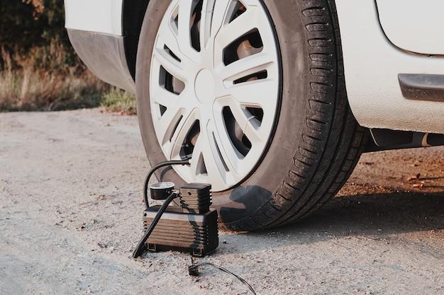 車のコンプレッサーでタイヤを膨らませます。