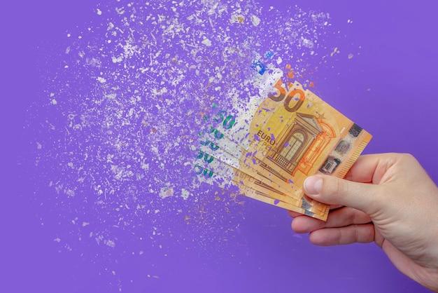 Инфляция евро. инфляция в европе, гиперинфляция. баннер с фиолетовым фоном. банкноты 50 евро распыляются в руке человека на фиолетовом фоне.