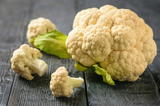 Inflorescence of cauliflower in a wooden spoon on a dark black table. healthy vegetarian diet.