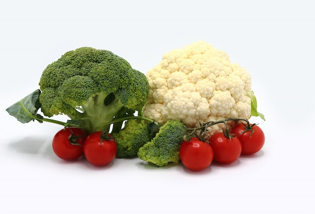 Inflorescences of broccoli and cauliflower and red ripe tomatoes on a light background.  close-up.
