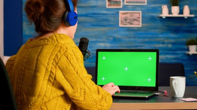 홈 스튜디오에서 팟 캐스트를 진행하는 동안 그린 스크린 노트북으로 작업하는 메시지에 인플 루 언서 응답