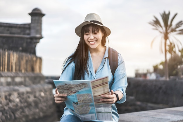 Influencer asian woman reading city map while traveling around the world