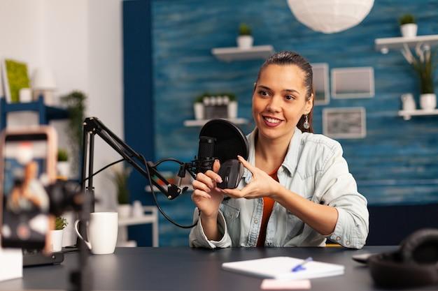 인플루언서 블로거가 팔로워를 위한 마우스 리뷰를 기록하면서 카메라를 보고 웃고 있습니다. 온라인 인터넷 팟캐스트 쇼를 위한 전문 장비로 비디오를 만드는 소셜 미디어의 새로운 미디어 스타.