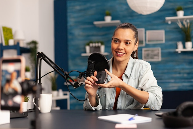 Influencer blogger smiling at camera while recording mouse review for followers. new media star on social media making video with professional equipment for online internet podcast show.