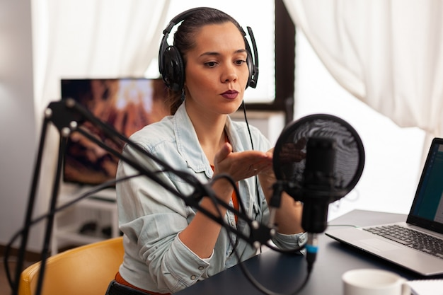 Influencer content creator blowing kisses in digital marketing concepts. blogger speaking and recording online talk show at studio using headset, professional microphone looking at camera for podcast