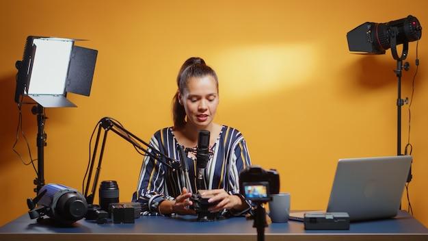 인플루언서 소녀는 전문 스튜디오에서 새로운 유체 헤드를 검토합니다. 웹 가입자 및 배포를 위한 비디오 장비에 대한 온라인 인터넷 콘텐츠를 만드는 소셜 미디어 스타, 디지털 vlog 이야기 파일