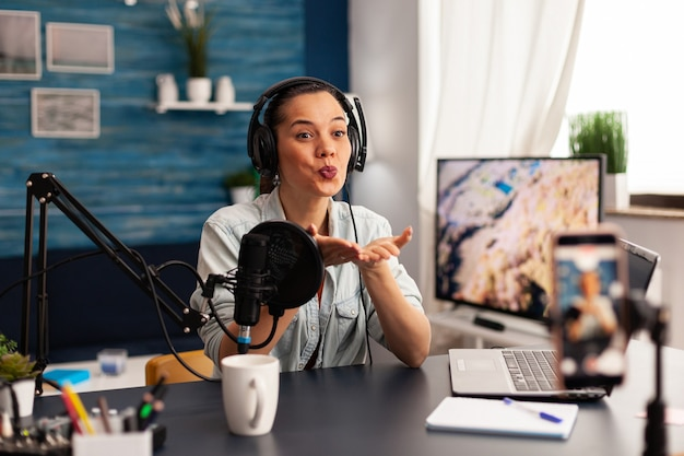 Influencer giving flying kiss while making new fashion series. creative vlogger recording video blog concept speaking and looking at smartphone on tripod home studio podcast