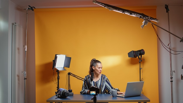 Influencer in her professional studio recording a new episode for subscribers. backstage of content creator new media star on social media for internet web online audience podcast episode microphone