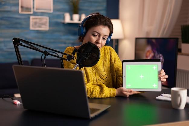 녹색 화면이있는 태블릿을 들고 홈 스터드에서 팟 캐스트하는 동안 마이크에 대고 말하는 영향력있는 사람.