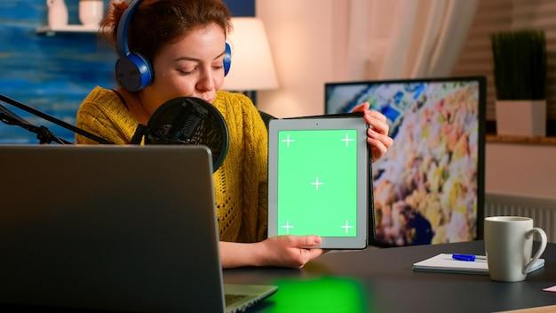 그린 스크린이있는 태블릿을 들고 홈 스튜디오에서 팟 캐스트하는 동안 마이크에 대고 말하는 영향력있는 사람