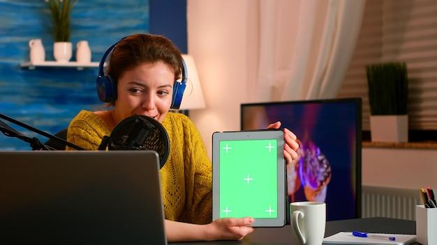 청중을위한 새로운 팟 캐스트 시리즈를 녹화하는 녹색 화면 디스플레이가있는 영향력있는 태블릿