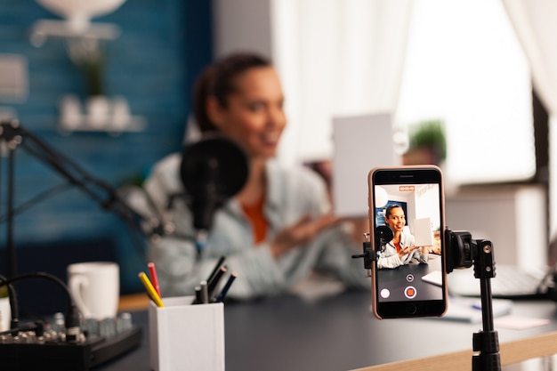 Influencer holding white gift box while recording videoblog for social media. creative content creator making broadcast concept speaking and looking at smartphone on tripod at home studio podcast