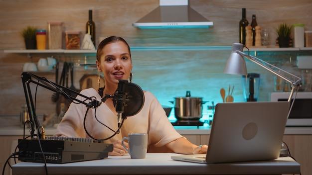 엔터테인먼트 산업의 영향력 있는 인물은 밤에 홈 스튜디오에서 방송하는 동안 웃고 소리를 확인합니다. 디지털 소셜 미디어 커뮤니케이션 녹음