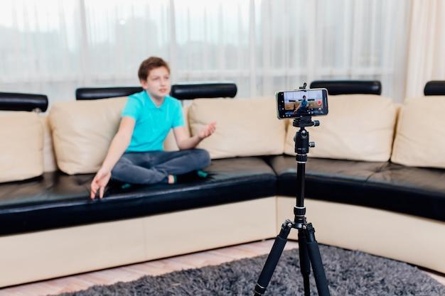 Влиятельный человек или подросток-ютубер, записывающий видео на смартфон дома
