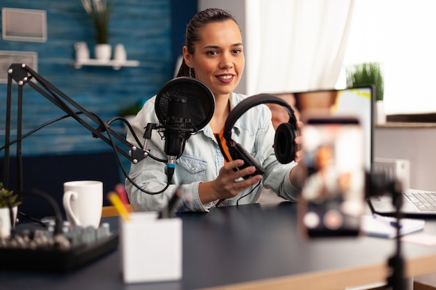 홈 스튜디오에서 비디오 블로그를 만드는 동안 카메라에 헤드폰을 선물하는 인플루언서. 청중을 위한 온라인 인터넷 웹 팟캐스트 선물을 녹음하는 창의적인 콘텐츠 제작자 인플루언서