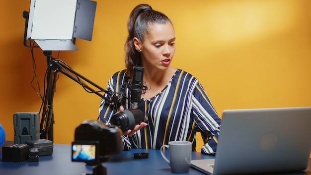 Influencer showing her public a new camera lens and reviewing it in professional studio set. content creator new media star influencer on social media talking video photo equipment for online internet