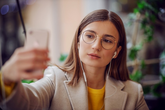 カフェのテラスに座って、耳にイヤホンを持って、ソーシャルメディアのために写真を撮るインフルエンサー。