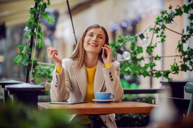 Influencer sitting on terrace of cafeteria, having coffee break and chatting on a phone with friend.