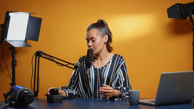 Influencer talking about new camera lens in her weekly podcast review episodes. content creator new media star on social media talking video photo equipment for online internet web show