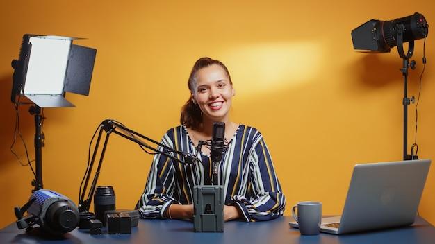 彼女のスタジオセットでプロのビデオ機器について話しているインフルエンサー。ソーシャルメディア上のコンテンツクリエーターニューメディアスターインフルエンサーによるプロのビデオ撮影ギアレビュー。
