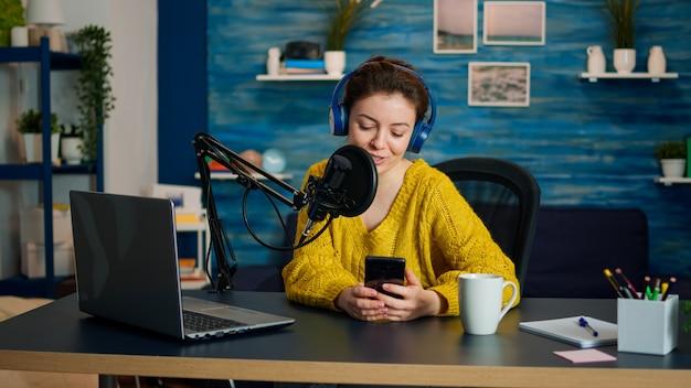 ソーシャルメディアでのライブ中にフォロワーと話しているときにラップトップを使用しているインフルエンサー。クリエイティブなオンラインショーオンエアプロダクションインターネット放送ホストストリーミングライブコンテンツ、デジタルビデオvlogの録画