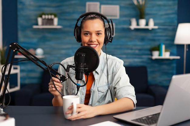 Youtubeチャンネルのホームスタジオで新しいポッドキャストシリーズを録音するヘッドフォンを身に着けているインフルエンサー。オンエアオンライン制作インターネット放送番組ホストストリーミングライブソーシャルメディアコンテンツ