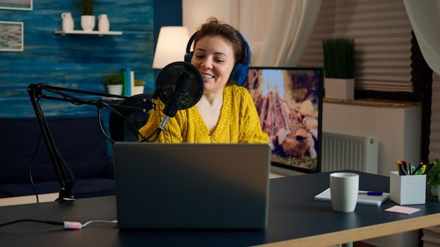 청중을 위한 새로운 팟캐스트 시리즈를 녹음하는 헤드폰을 끼고 있는 인플루언서. 온에어 온라인 제작 인터넷 방송 쇼 호스트 인터넷 웹을 사용하여 디지털 소셜 미디어용 라이브 콘텐츠 스트리밍