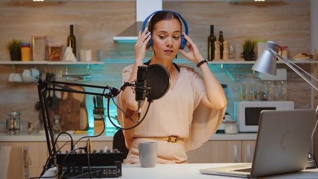 彼女の聴衆のために新しいポッドキャストシリーズを録音するヘッドフォンを身に着けているインフルエンサー。オンエアオンライン制作インターネット放送番組ホストストリーミングライブコンテンツ、デジタルソーシャルメディア通信の記録