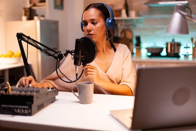 헤드폰을 끼고 청중을 위한 새로운 팟캐스트 시리즈를 녹음하는 인플루언서. 온에어 온라인 제작 인터넷 방송 쇼 호스트 스트리밍 라이브 콘텐츠, 디지털 소셜 미디어 커뮤니케이션 녹음