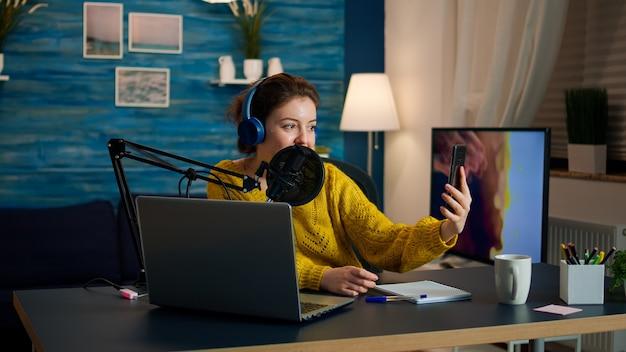 聴衆のために自分撮り録音ポッドキャストシリーズを撮るために電話を使用するヘッドフォンを持ったインフルエンサー。オンエアオンライン制作インターネット放送ショーホストストリーミングライブコンテンツデジタルソーシャルメディア