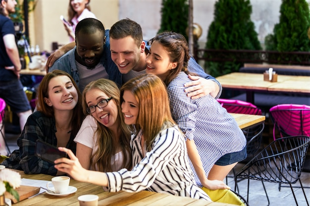 Неформальная встреча лучших друзей в уютном кафе и фотографирование селфи на смартфоне