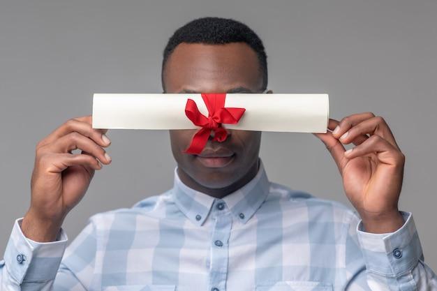 Информация. афроамериканец в клетчатой рубашке держит важный сверток, перевязанный красной лентой на уровне глаз