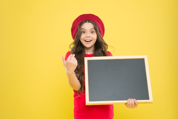 Information board. fashion news. small girl kid with school backboard, copy space. back to school. interesting info. big sales. child on yellow background. happy girl in french beret. small publisher.