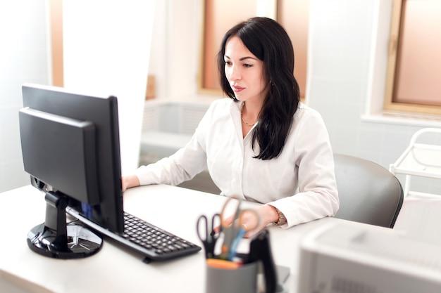 必要な情報。集中して見えるコンピューターで作業している白いローブの暗い髪の医者