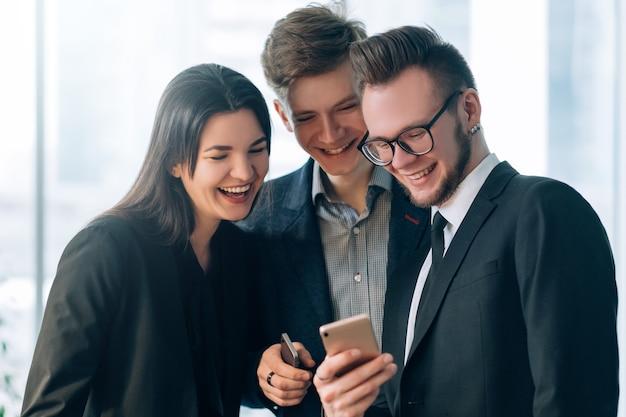 情報技術。現代のオフィスライフスタイル。男のスマートフォンで楽しいコンテンツを笑っている若い同僚。