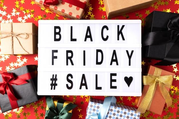 Информационный лайтбокс с надписью черная пятница в центре подарочной коробки на ярком фоне