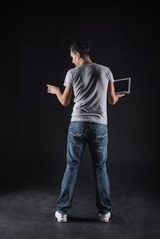 Информационное пространство. хороший умный молодой человек держит ноутбук и стоит перед компьютером, используя компьютерные технологии