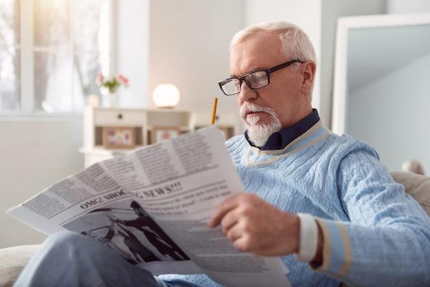 Информационная статья. очаровательный пожилой мужчина в очках читает статью в газете и отмечает карандашом интересные места