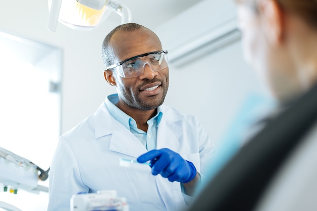 유익한 대화. 쾌활한 젊은 치과 의사가 여성 환자와 치과 플라크에 대해 이야기하고 그 외모를 예방하는 방법을 알려줍니다.