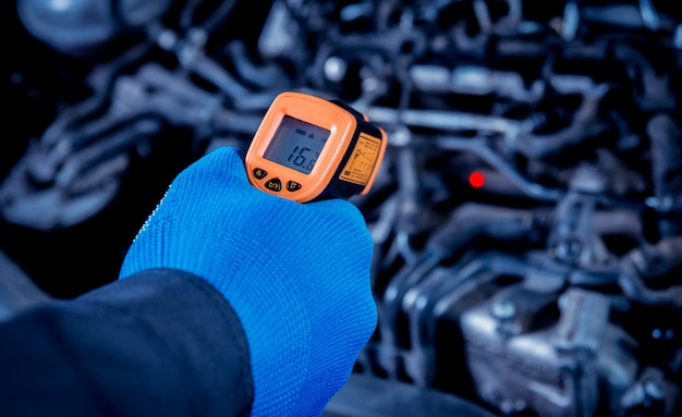 Infrared laser thermometer in hand. motor temperature measurement