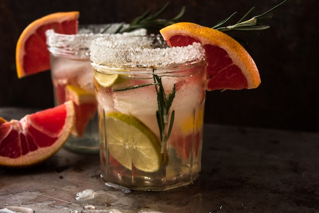 Infused detox water with grapefruit and rosemary in glass bottle on gray wooden table. diet healthy eating and weight loss concept, copy space for text