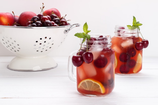 Infused flavored water with cherry, lemon and mint