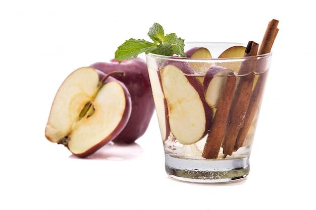 リンゴとシナモンの新鮮なフルーツ水を注ぎました。 w上に分離