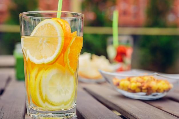 屋外の木製テーブルにフルーツウォーターカクテルと緑の野菜のスムージーを注入。健康的なオーガニックサマードリンクのコンセプトです。