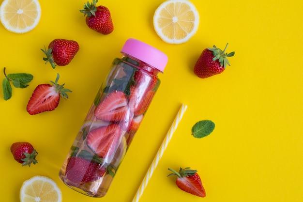 Настаивается или детокс воды с клубникой и лимоном в бутылке на желтой поверхности. крупным планом.