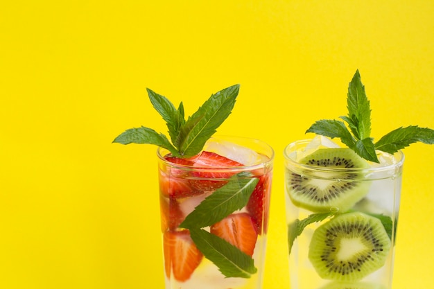 Infused water or lemonade with strawberry, kiwi, ice and  mint  in the two glasses