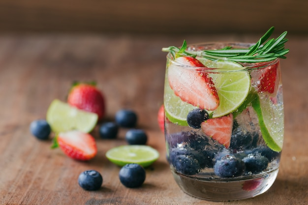 Infused water or mixed fruit mojito with blueberry strawberry and lemon in sparkling miner