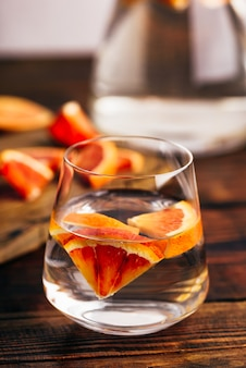Infused water with bloody oranges in drinking glass